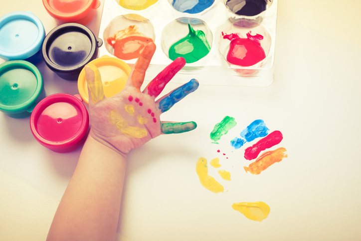 Kinderhand mit Fingerfarben bemalt