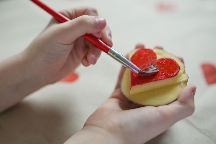 Kind bemalt einen Kartoffelstempel mit Herzmotiv