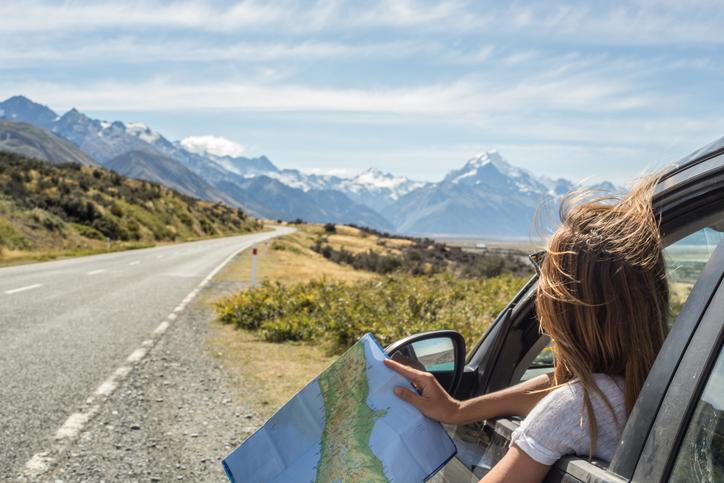 Frau mit Landkarte vor einer Berglandschaft