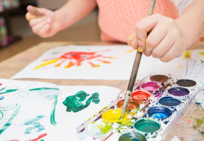 Kind malt mit Wasserfarben ein Bild