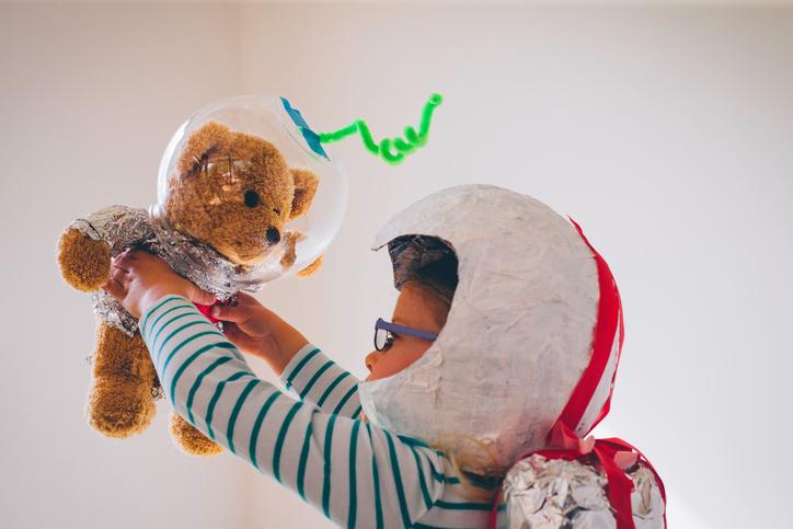 Kind spielt mit seinem Teddy Astronaut