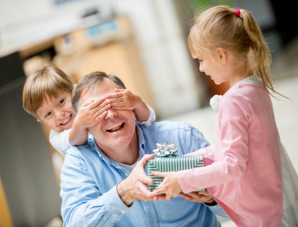 Vater wird von Kindern zum Vatertag mit einem Geschenk überrascht