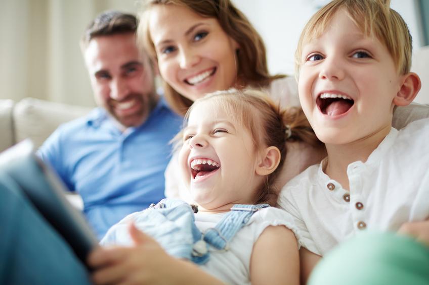 Eltern und Kinder lachen beim Betrachten eines Fotoalbums