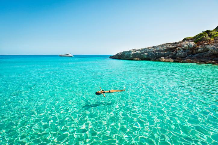Türkisfarbenes Wasser und auf dem Rücken schwimmende Frau
