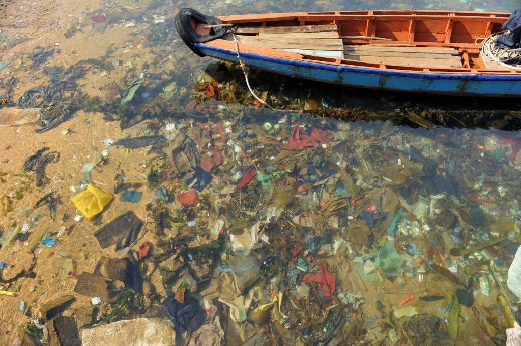 Boot über von Müll verschmutzten Wasser