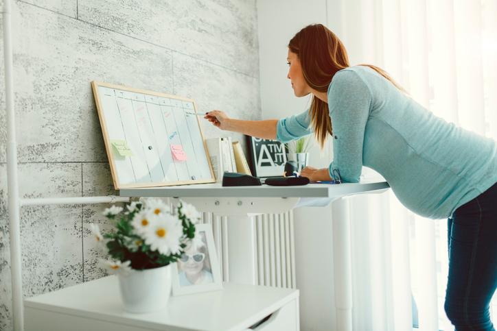 Schwangere Frau liest eine To-Do-Liste auf einer Magnettafel